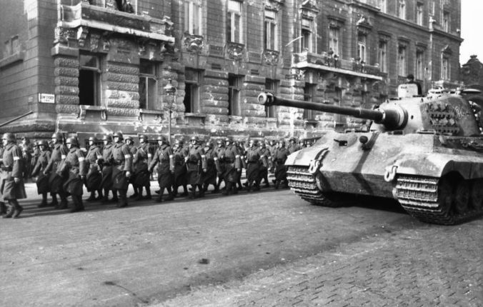 Hungarian militia from the Arrow Cross Party pass a german Tiger II in Budapest, October 1944.
